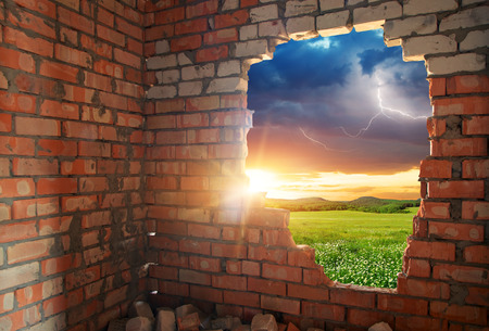 the hole: Broken bricks wal and landscape. Conceptual composition.