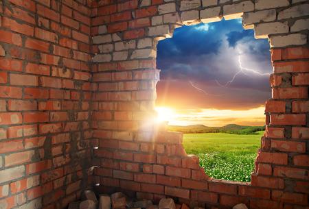 pared rota: Ladrillos rotos wal y paisaje. Composición conceptual. Foto de archivo
