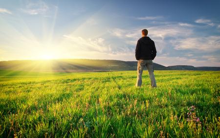 sol naciente: Hombre en el prado verde. Conceptual escena. Foto de archivo