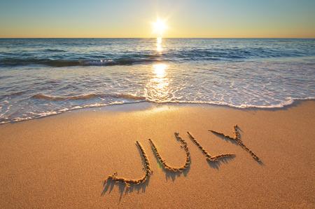 calendario julio: Julio palabra sobre la arena del mar. Naturaleza cpmposition. Foto de archivo