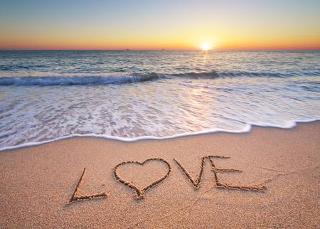 escribiendo: Lowe sobre la arena del mar. Composición de la naturaleza. Foto de archivo