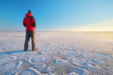 Man on winter ice. Hiking scene.