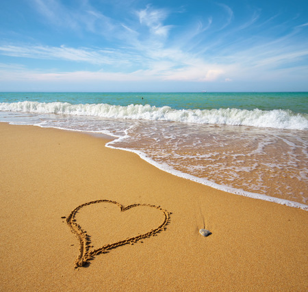 Heart on the sand of a beach. Romantic composition.