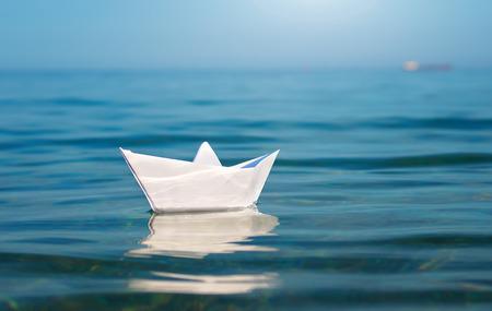 Papier stuk speelgoed schip en de diepblauwe zee. Conceptueel ontwerp.