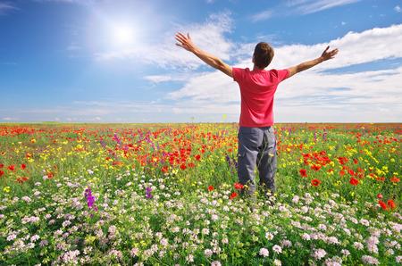 Man in spring meadow of flower. Emotional scene. Standard-Bild