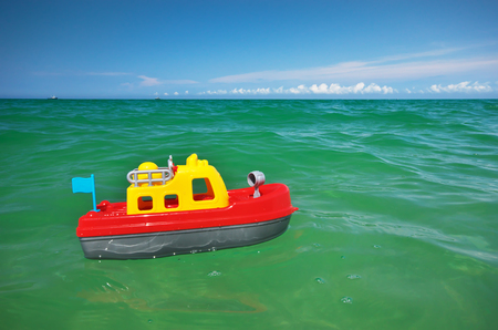 plastic made: Toy ship boat and sea wave. Conceptual design. Stock Photo