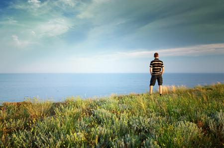edge of cliff: Man on the edge. Cliff of mountain and sea. Conceptual scene. Stock Photo
