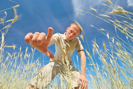 reaching hand: Man find some in grass. Funny scene.