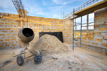 Home building. Concrete mixer and heap of sand. Architecture and industry composition.