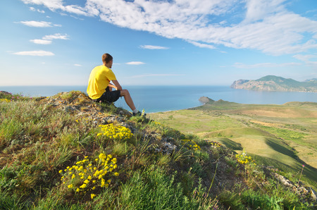 Man looking on the sea and mountain landscape. Stock Photo