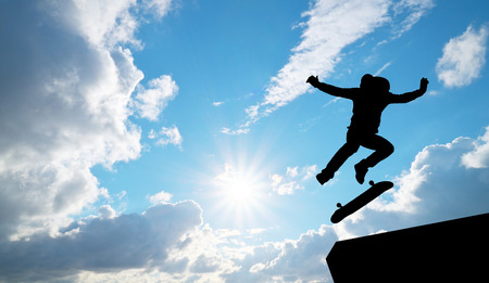Skater jump silhouette and blue sky. Element of design. Stock Photo