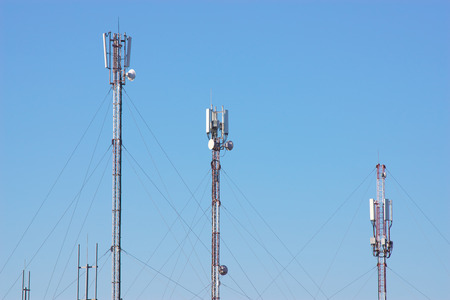 Telecommunication radio antenna towers. Technology construction on sky background.