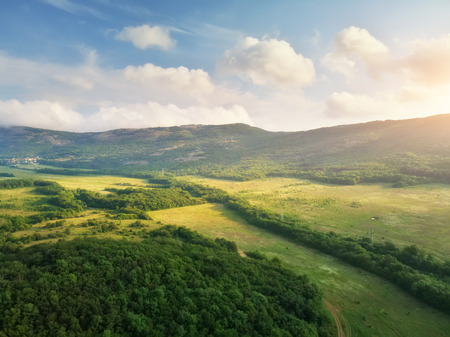 Scenic aerial view of beautiful landscape of the valley and hills in the background and dramatic clouds in the sky.