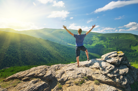Man on peak of mountain reach to the sun. Emotional scene.