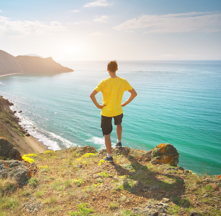 Man standing on sea and mountain landscape. Conceptual and emotional scene. Stock Photo