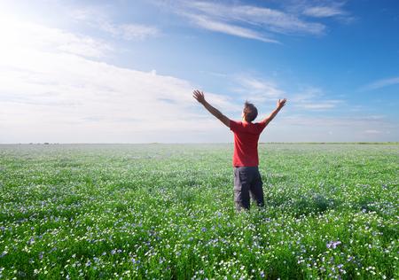Hombre en prado verde y flor de lino alcance al sol en el cielo azul profundo. Escena conceptual. Foto de archivo