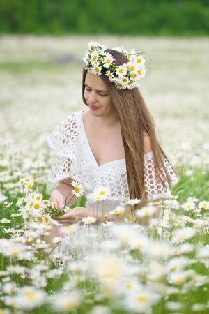 Cute girl in camomile meadow. Beautiful outdoor portrait scene.