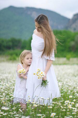 Szczęśliwa matka i córka w dużej górskiej łące rumianku. Scena emocjonalna, miłosna i opiekuńcza.