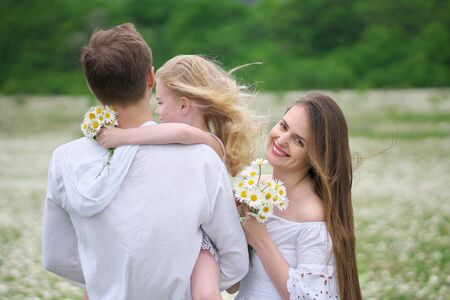 Happy family on big camomile mountain meadow. Emotional, love and care scene. Stockfoto