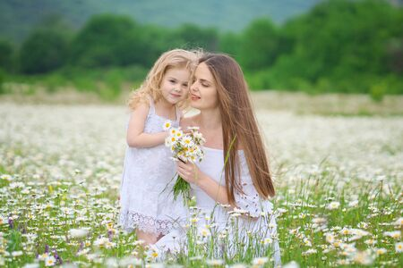 Happy mother and daughter in big camomile mountain meadow. Emotional, love and care scene.