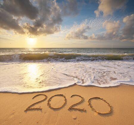Año 2020 en la orilla del mar durante la puesta de sol. Elemento de diseño.