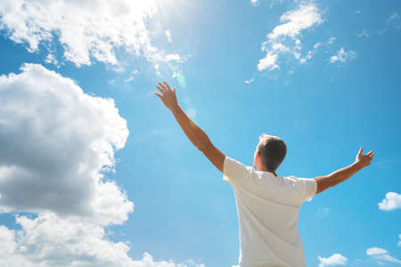 Man strive hands to the deep blue sky and sun. Religion and conceptual scene. Worship to God.