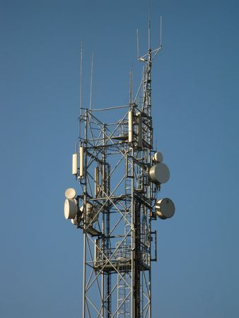 affixed: Various radio and GSM antenna affixed to the mast against a blue sky  Stock Photo