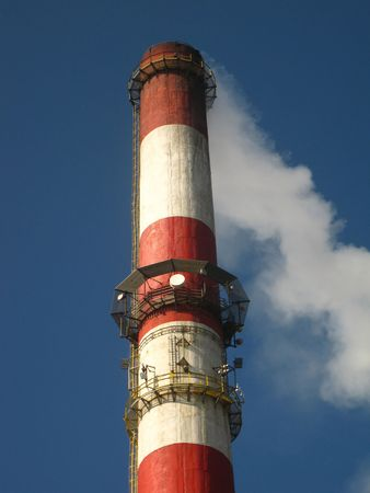 red and white chimney with outgoing exhaust gases or steam  photo