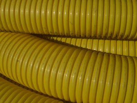 cesspool: yellow  plastic hoce, snake before digging into the ground - a fragment  Stock Photo