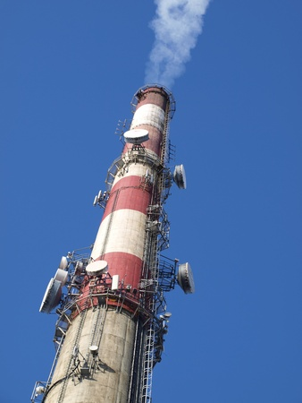 tall chimney: a tall chimney with smoke visible against the blue sky