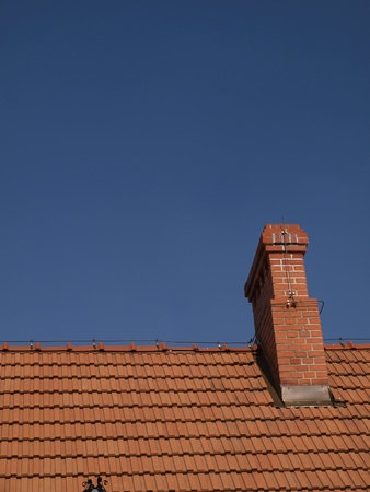 red-brick chimneys on the roof of red tiles photo