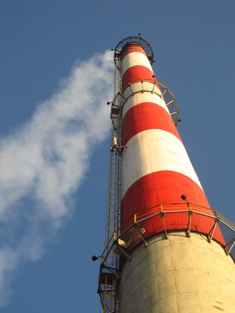 high white-red chimney against a blue cloudless sky photo