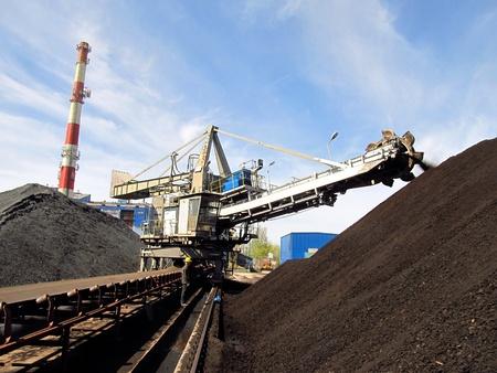 carbone: Stacker con un mucchio di carbone accanto allo stabilimento