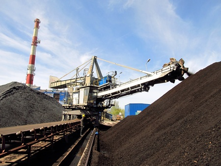 Stacker with a heap of coal next to the plant Stock Photo - 13483396