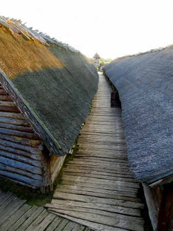 wooden buildings and thatched roofs, old settlement, part of the archaeological museum in Poland Biskupin Editorial