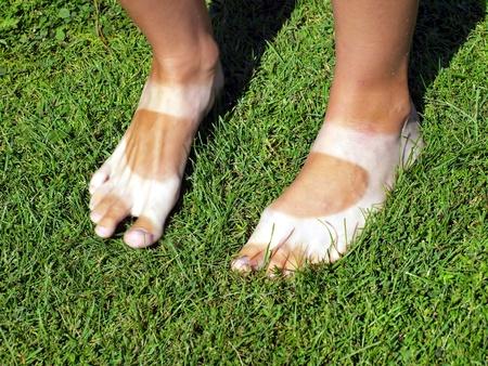 特徴的な方法で日焼けした日にサンダルで歩く女性の足