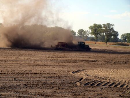 a large cloud of dust during work on a dry field farming    Stock Photo