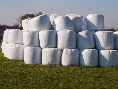 straw bales stored in a plastic bag in the meadow as a background