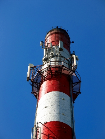 old white and red brick industrial chimney or concrete with one built GSM antenna system along with parts of other plants Stock Photo - 16505115