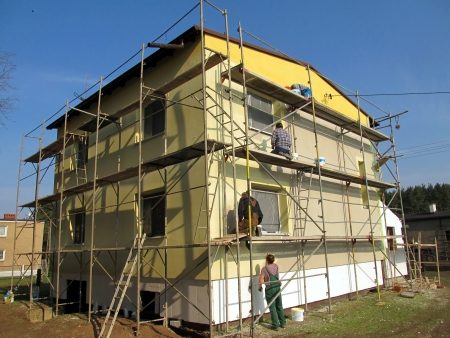 The construction works. Priming the facade of the building before applying the plaster,
