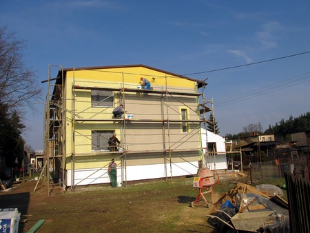 priming: The construction works. Priming the facade of the building before applying the plaster,