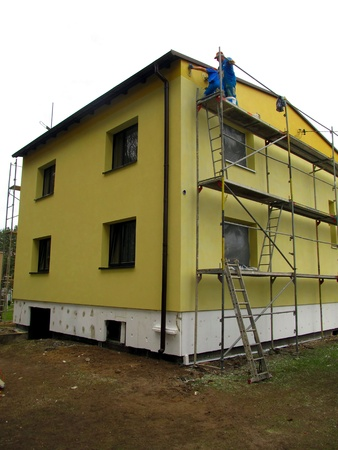 The construction works. Application of colored plaster on the facade of the building detached. Imagens