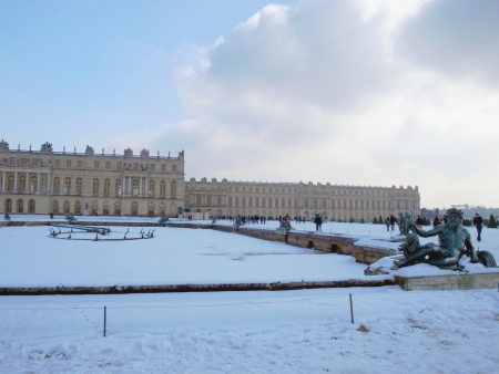 garden sculptures and pond in front of the royal residence at Versailles near Paris in France in winter scenery, the snow photo