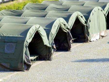 青少年のためのキャンプとして舗装された区域にいくつかの大きな軍用テント
