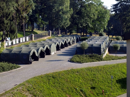 several large military tents on the paved area as a camp for youth Stock Photo