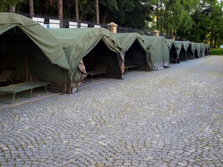 several large military tents on the paved area as a camp for youth photo