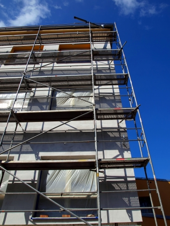 detail of the facade of a large building at the insulating walls with visible scaffolding all over the wall Editorial