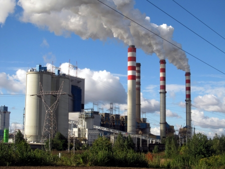 browncoal: brown-coal power plant with chimney giving off large amounts of gas to the blue sky Stock Photo
