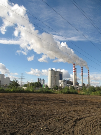 amounts: brown-coal power plant with chimney giving off large amounts of gas to the blue sky Stock Photo