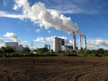 brown-coal power plant with chimney giving off large amounts of gas to the blue sky Stock Photo